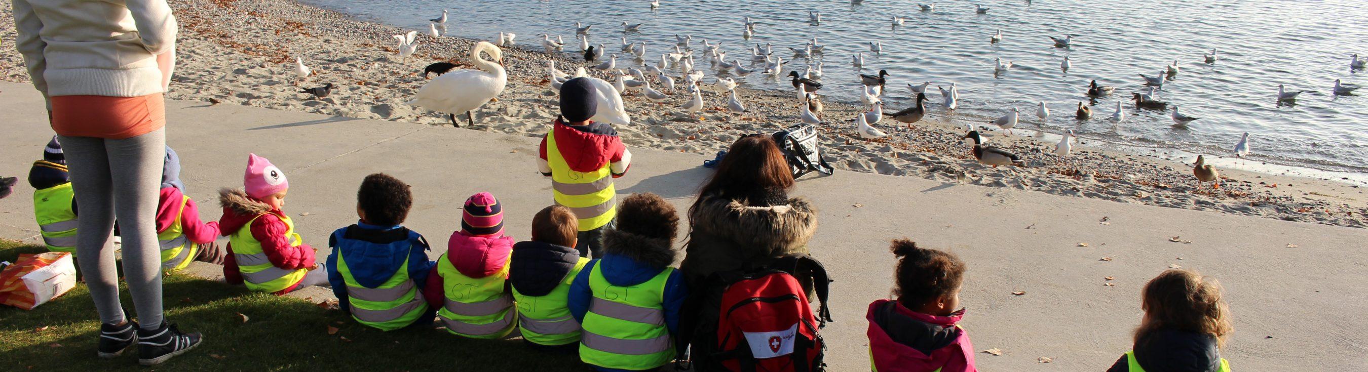 enfants assis au bord du lac avec leur éducatrice